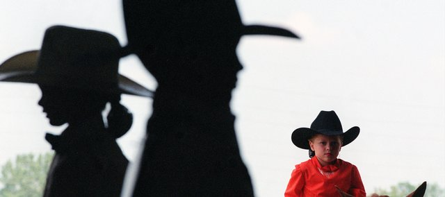 Two young contestants in a horse show are silhouetted. The photographer achieved this effect by standing inside a dark arena and aiming the camera outside into the bright sunlight. While the photographer was framed on the two riders at center and right, the third cowgirl rode through to complete the photograph.