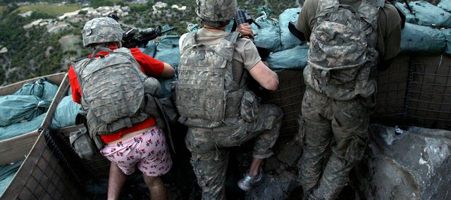 "In this May 11 file photo, soldiers from the U.S. Army First Battalion, 26th Infantry take defensive positions at firebase Restrepo after receiving fire from Taliban positions in the Korengal Valley of Afghanistan's Kunar Province. Spc. Zachery Boyd of Fort Worth, Texas, far left was wearing ""I love NY"" boxer shorts after rushing from his sleeping quarters to join his fellow platoon members. From far right is Spc. Cecil Montgomery of Many, La., and Jordan Custer of Spokane, Wash., center."