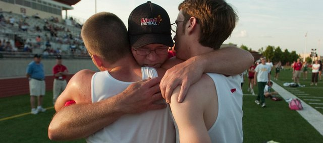Lawrence High distance runners Ben Wilson, left, and Roy Wedge hug Lions coach Jack Hood. The LHS boys team finished second at the Class 6A regional track and field meet Friday at Shawnee Mission North.