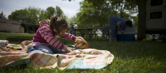Hannah Scott, 7, Topeka, plays with a relative's dog, Kaden, while her family sets up at the Cedar Ridge campground at Clinton Lake State Park.