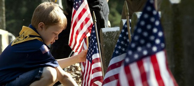 Cub Scout Matthew Wellman, 8, of Troop 3052 places a flag at the headstone of a Union veteran of the Civil War Saturday, May 23, 2009 at Oak Hill Cemetery. Several Boy Scout and Cub Scout troops helped members of Sons of Union Veterans of the Civil War locate around 300 markers for flags throughout Oak Hill and several other cemeteries around Lawrence.