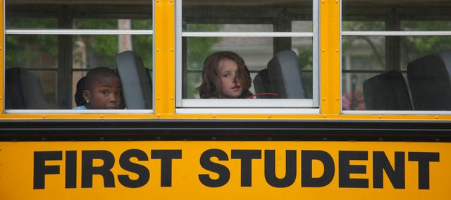 Schwegler School students on a First Student bus wait for a ride home after school Wednesday. School district budget cuts are eliminating bus rides for children living less than 2.5 miles from school.