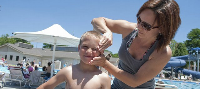Alden Hunt, 8, Lawrence, gets sunscreen applied to his face by his mother Christy Hunt as the two prepared for an afternoon at the Lawrence Outdoor Pool in 2009.