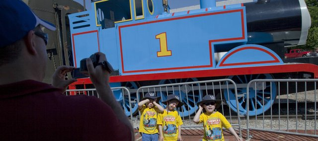 Ryan Steiner, 4, left and his twin brothers Zach and Cole, 6, have their photograph taken by their father, Chad Steiner, Overland Park, in front of Thomas the Tank Engineª at the Midland Railway in Baldwin City. The storybook engine will give rides at the Baldwin Depot and other activities including a petting zoo and a magician will take place this Friday to June 7.
