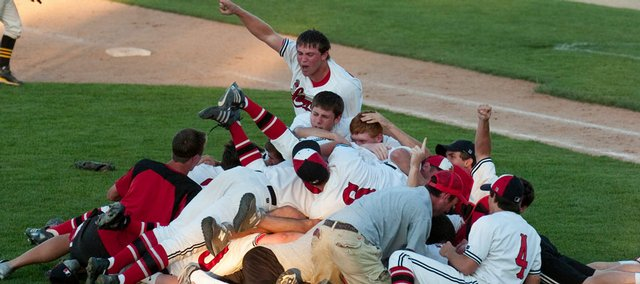 Lawrence High baseball players dog-pile on each other after defeating Shawnee Mission West, 3-2, in the Class 6A state championship game in Lenexa.