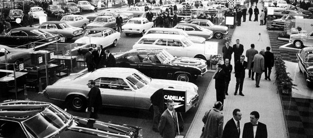 This Jan. 16, 1969, file photo shows exhibitors at the Brussels Car Show at the Plais Du Centenaire, in Brussels. General Motors survived wars, strikes and the Great Depression churning out Chevys, Cadillacs and other vehicles that often defined their owners' status in life. But less than a year into its second 100 years, it's coming to the end of a road, ushered by the government into bankruptcy protection.