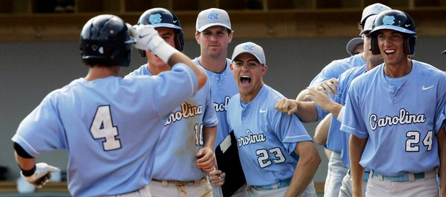 North Carolina's Garrett Gore (4) is congratulated by Kyle Seager (10), Matt Harrison (23) and Ryan Graepel (24) after Gore's grand slam home run against Kansas University. The slam helped the Tar Heels oust KU, 12-1, Sunday from the NCAA regional in Chapel Hill, N.C.