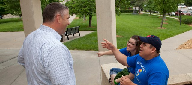 Lawrence Special Olympians Becky Saathoff, 28, and Brady Tanner, 29, joke with Sheriff's Office Lt. Doug Woods on Thursday outside of the Douglas County Judicial and Law Enforcement Center. Woods is one of 38 local law enforcement members who will be participating in the Special Olympics Torch Run on Wednesday, and both Saathoff and Tanner will compete in the Kansas Special Olympics on Friday in Wichita.