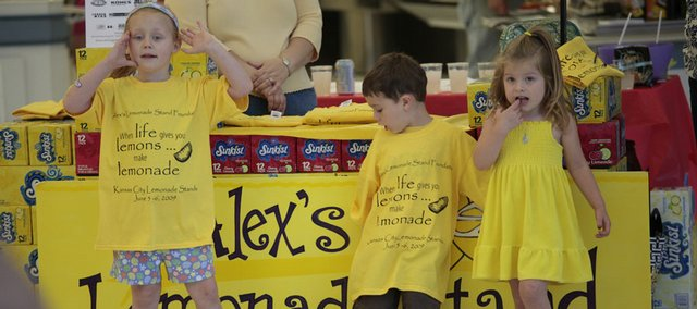 "At left, Isabella Vermooten, 5, greets shoppers Friday with a shout of ""Would you like to buy some lemonade?"" at the Hy-Vee store at 4000 W. Sixth St. Isabella was joined by volunteers Benjamin Willems, 3 and Campbell Helling, 3. The children were raising money to fight childhood cancer with the Alex's Lemonade Stand Foundation. The fundraiser continues Saturday at area Hy-Vee stores."