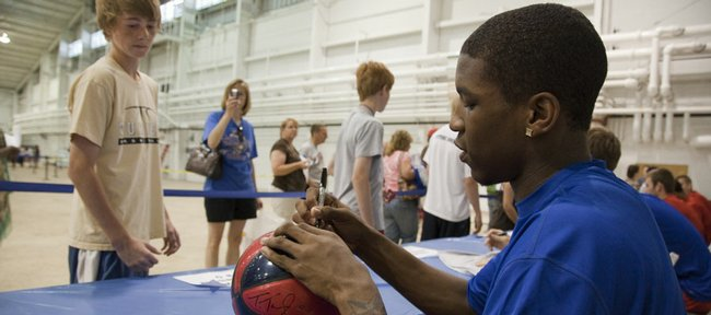 Kansas University freshman Thomas Robinson signs an autograph for Bill Self Basketball camper Sean Novak, 13, of Overland Park. Self's camp opened Sunday.