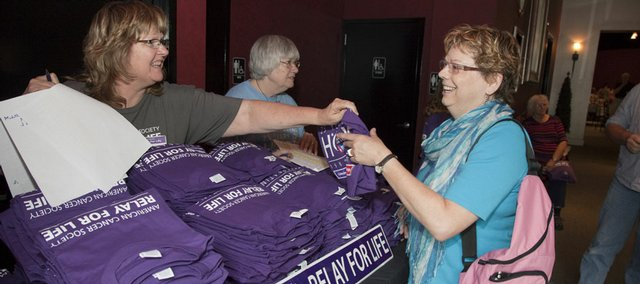 Karen Wesbecker, left, hands a Relay for Life T-shirt to Monica Gutierrez of Lawrence at a Cancer Survivors' Day dinner at Maceli's. The Relay for Life will be Friday.