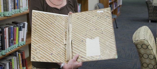 Lea Currie, head of collection development for KU libraries, displays a copy of a book from the Watson Library collection that was stripped of several pages. The folio book was on the archeology of Delphi, one of the most important sites of ancient Greece.
