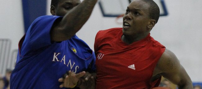 Kansas guard Sherron Collins tries to block the path of former KU player Russell Robinson. Current and former Jayhawk players scrimmaged Wednesday at Horejsi Center during the Bill Self camp.