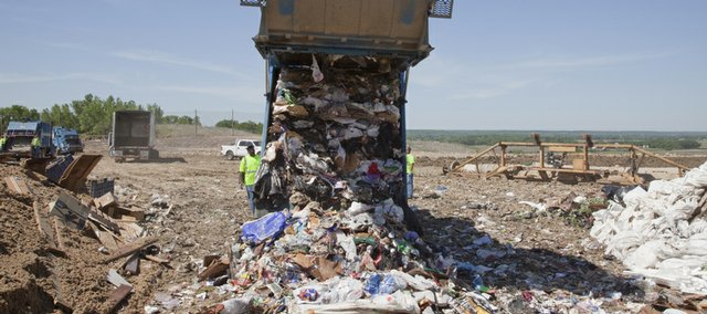 A city of Lawrence trash truck unloads a full 21,000-pound cargo of household refuse at the Lawrence sanitary landfill.