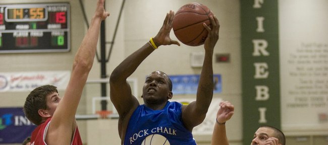 Former Kansas player Russell Robinson jumps between Christian Moody, left, and Chris Zerbe on his way to the basket during the Rock Chalk Roundball Classic at Free State High. Robinson played with the Reno Bighorns of the NBA Developmental League last season.