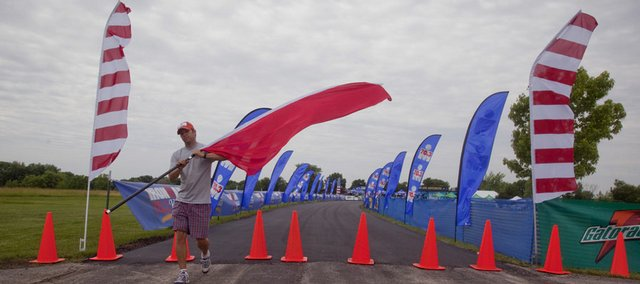 Andre LaPAR sets up flags Friday at Clinton State Park in preparation for this weekend's Ironman 70.3 Kansas. Below: Triathletes hit the water at Clinton Lake at the start of last year's Ironman event.