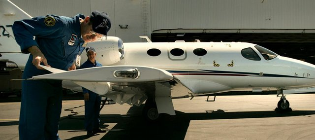 Test pilots do a preflight inspection before making a test flight in a Cessna Citation Mustang business jet in this June 15, 2005, file photo in Wichita. Aircraft maker Cessna announced 1,300 more layoffs Friday in a new round of cuts.