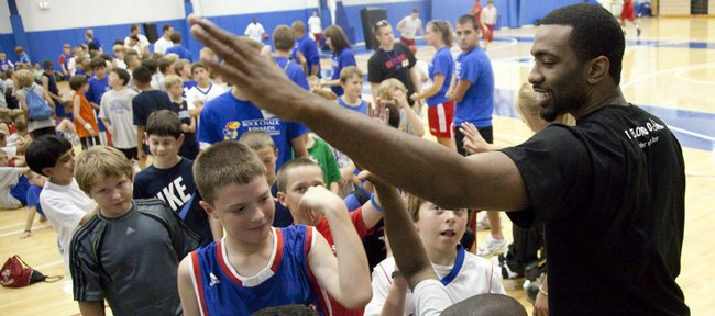 Former Kansas basketball player Keith Langford gives out high fives after speaking to the Bill Self campers on Monday at Horejsi Center. Langford has agreed to play in Russia next season.