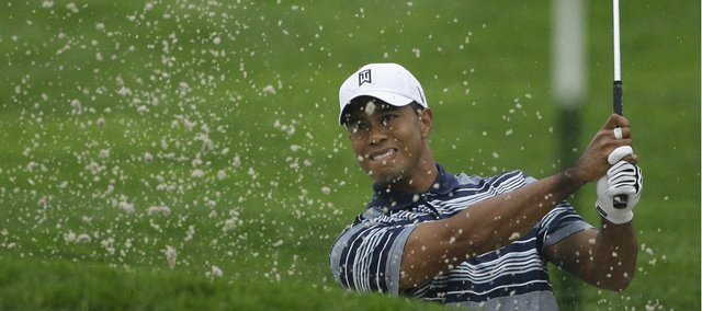 Defending U.S. Open champion Tiger Woods chips out of a bunker on the first hole during the first round of the U.S. Open Golf Championship at Bethpage Black on Thursday in Farmingdale, N.Y. Woods completed six holes before rain caused officials to call off play for the day.