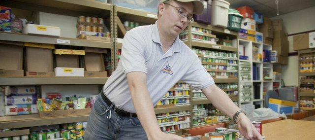 Andy Brown, human services director at the Ballard Center, 708 Elm St., sorts food items at the center's food pantry. Food banks and nonprofits in Lawrence have joined an online virtual food bank network that allows donors to give money online to local food banks.