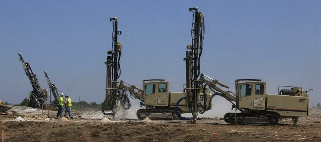 Drilling machines crawl along a hillside south of Lawrence on Thursday drilling holes some 20 feet deep for explosive charges to loosen the ground, just one part of the ongoing construction on U.S. 59 Highway between Ottawa and Lawrence. The project is well under way in Douglas County.