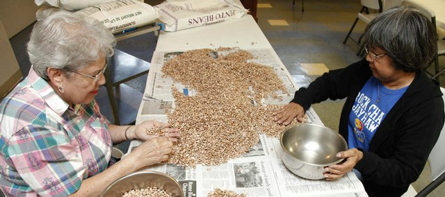 Bert Bermudez, left, and Irene Langford sort through pinto beans Friday to make sure they are clean and ready for cooking for the St. John's Mexican Fiesta. About 250 pounds of beans are used for the event.