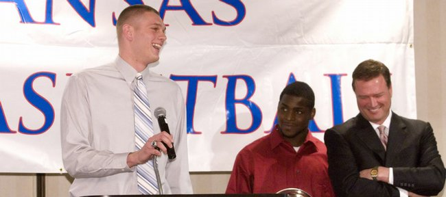Kansas center Cole Aldrich, left, entertains the crowd at the basketball awards banquet April 13 at the Holidome, next to Sherron Collins, center, and coach Bill Self. Aldrich and Collins recently expressed no regrets in electing to stay in school for another year. The NBA Draft is tonight in New York.