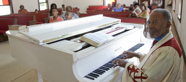 St. James AME pastor Theodore Lee looks to the choir and starts off a song during a Sunday service at the the church.