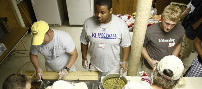 Kansas University defensive tackle Richard Johnson Jr., center, and linebacker Huldon Tharp, right, fill plates in the serving line with volunteer and Lawrence resident Dave Kelsey, left, on Sunday at the Lawrence Interdenominational Nutrition Kitchen.  Johnson started eight games on the defensive line last season for the Jayhawks before being hampered by an injury.