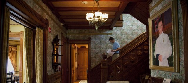 Andre Bollaert, executive director of the Castle Tea Room, makes his way down the main staircase and into the entry hall of the home.