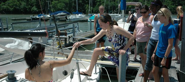 Frances Zhu, left, of Overland Park, helps Mary Kate Jenks, of Leawood, board an autonomous boat designed by a Kansas University engineering student as part of Project Discovery last month.