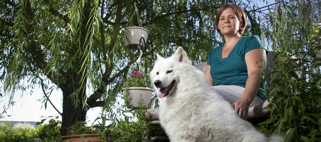 Lawrence resident Pam Heikes and her dog Sage are pictured in the garden of their home. Heikes has found that designating an area for a little bit of digging by pets can help to save the rest of the garden.