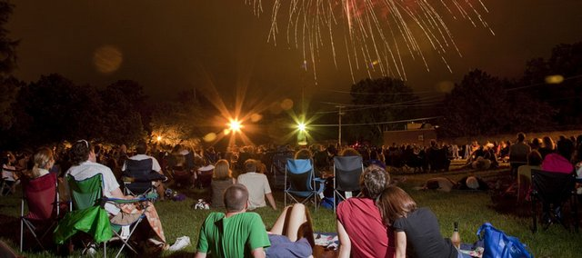 People sit in Constant Park downtown to watch the 2009 annual fireworks display put on by the Lawrence Jaycees.
