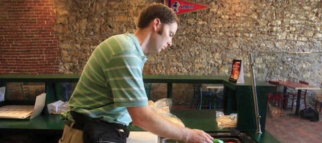 Andrew Stull, environmental health specialist for Lawrence and Douglas County, makes a routine inspection recently at the Pita Pit in downtown Lawrence.