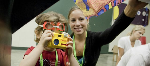 Emma Day, 5, uses a toy camera to take photographs of fish in the sea lab during the Sertoma-Schiefelbusch Communications Camp on Wednesday at the Douglas County 4-H Fairgrounds. At right is Erin Gunzelman, a KU graduate student in speech and language pathology.