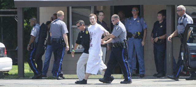 Lawrence police and Douglas County Sheriff's officers take a man into custody at the Jayhawk Motel, 1004 North 2nd Stree,t shortly after noon Thursday. Up to 10 law enforcement officers had surrounded a room at the motel and had it under observation for over an hour before the man was apprehended.