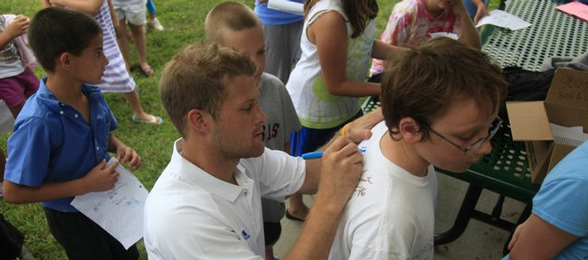 Richard Gwin/Journal-World Photo.Members of the KU football team were on hand Friday at Langston Hughes Elementary School where the Lawrence Boys and girls Club is having a summer session, as the tema signed autographs for many eager kids. Tristan Delnevo 11, gets his t shirt signed by Todd Reesing.