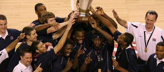 The USA team celebrates its championship victory over Greece. Taylor, the only player wearing a headband, is holding the trophy with his left hand in the front row.