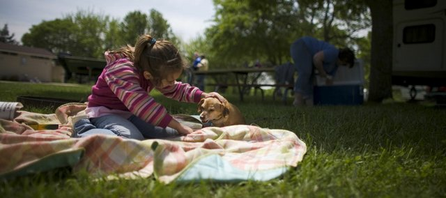 Hannah Scott, 7, Topeka, plays with Kaden while her family camps at the Cedar Ridge campground at Clinton Lake in this file photo from May. Kids, animals and adults can all be bitten by chiggers climbing out of the grass.