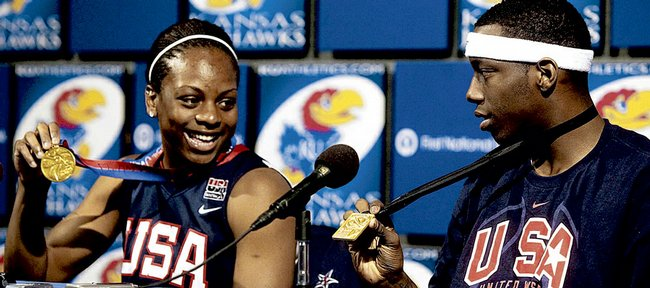 Danielle McCray, left, smiles as she and Tyshawn Taylor display their gold medals from this year's World Championships. McCray and Taylor spoke about the titles at a news conference on Wednesday at Hadl Auditorium.