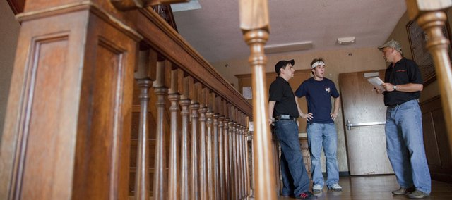 From left, Rob Garcia, Shawnee, KU junior Zach Williams, Olathe, and Bill Joeckel, Osawatamie, gather on a second floor landing at the KU Sigma Nu house Saturday evening during a tour of the fraternity house led by Williams. Williams was recounting stories of mysterious events in the house prior to a team of Elite Paranormal and K.C. Paranormal Studies members doing a ghost investigation Saturday night.