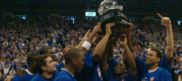 Kansas University basketball players hoist their newly-earned Big 12 regular season title trophy. The Jayhawks defeated Texas in March 2007 to take the regular season title outright and notch the program's 1,900th victory.