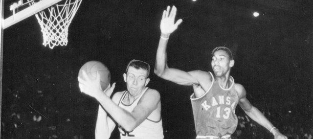 Kansas University basketball player Wilt Chamberlain (#13) defends an SMU player as Gene Elstun (#12) looks on in this March 15, 1957 file photo. Chamberlain and the Jayhawks defeated SMU to record the 800th victory in KU history. The 1957 team went on to finish as the national runner-up.