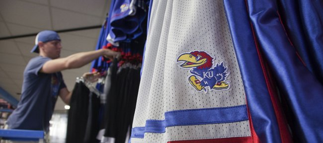 Sports Dome manager Brad Wilson arranges a new selection of KU shorts in the store, 1000 Mass. Sports Dome sells officially licensed Kansas University merchandise.