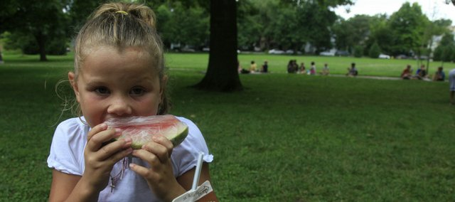 Deciana Jaillite, 6, bites into a slice of watermelon during a Summer Lunch Program meal last week in South Park. More than 65 children took their noon meal in the park last Tuesday.