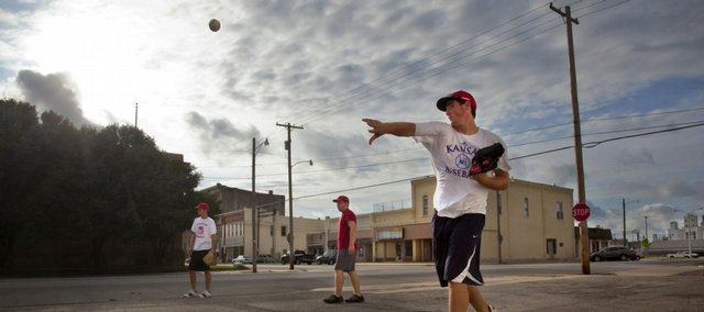 Ottawa Post 60 players Chase Dengel, right, Dylan Nelson and Adam Maxwell play catch in a parking lot near the intersection of Second and Hickory streets as the sky clears from the rain Tuesday, July 28, 2009 in Ottawa. The legion baseball team, which is 39-0 on the season is hoping to carry their undefeated streak through the state tournament.