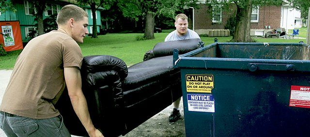 Karl Gustke, left, and his friend Shawn McMahon set a couch down next to a Dumpster on Thursday after discovering it wouldn't fit inside. Thursday was moving day for many people, especially Kansas University students, as rental leases neared their expiration date.