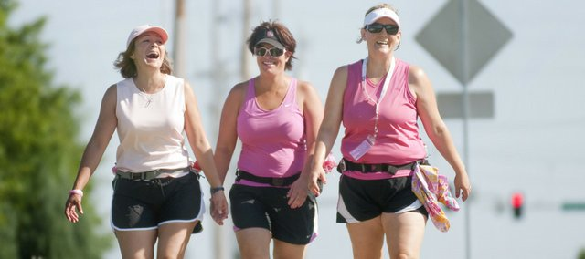 "Shari Anderson, left, Julie Embrey and Susan Cary walk along Folks Road on Friday as they train for the 2009 Breast Cancer 3-Day, a fundraiser in Chicago from Aug. 7 through Aug. 9. The group has walked more than 500 miles since February and has raised more than $9,000 to benefit Susan G. Komen for the Cure. The women named themselves ""Amy's ACEs"" in honor of their friend Amy Laughlin, who battled breast cancer and died on Nov. 9, 2008."
