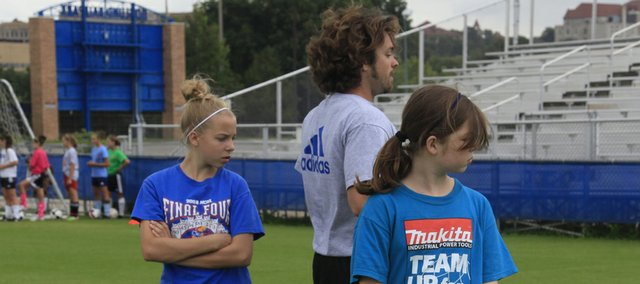 From left, Kate Mays 12, and Addison Campbell 13, listen to Todd Trahan, instructor, on the art of setting up a shot, at Kansas University's soccer fields.