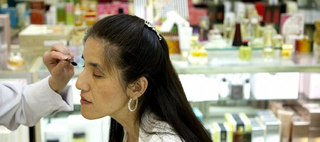 Chikako Mochizuki, a doctoral student at Kansas University who is blind, has mascara applied during a makeover by Clinique counter manager Sue Hopkins at Weaver's department store. '